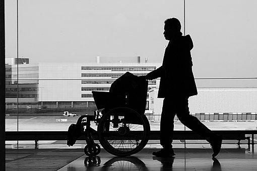 Silhouette d'un homme poussant un fauteuil roulant