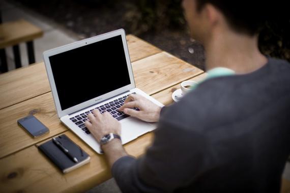 Homme assis devant un ordinateur portable, mains sur le clavier