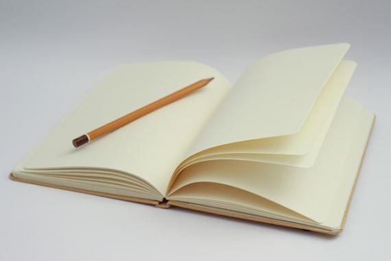 Crayon posé sur un carnet de notes ouvert à une page blanche