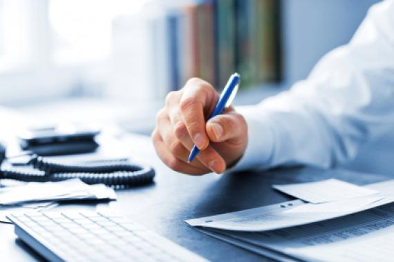 main munie d'un stylo qui écrit sur un carnet