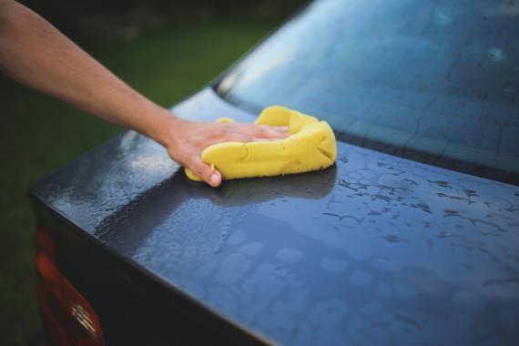 Action de quelqu'un lavant une voiture avec une éponge