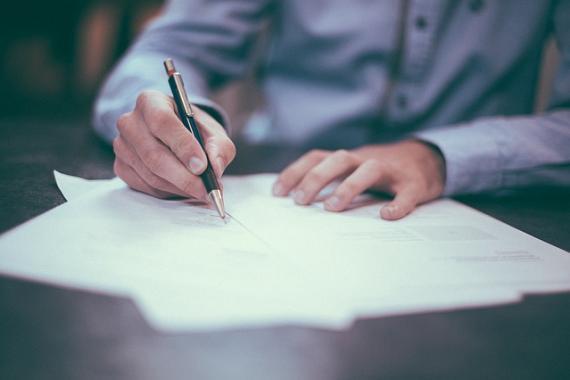 Homme attablé, tenant un stylo à plume dans ses mains, s'apprêtant à signer un document