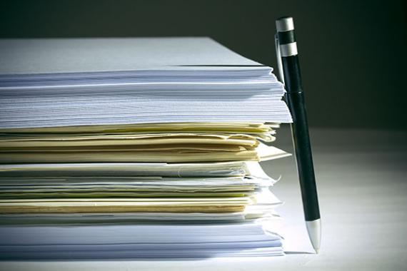 Stylo à bille appuyé sur une pile de papiers