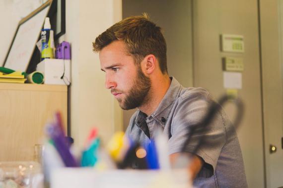 Jeune homme de profil au travail dans un bureau