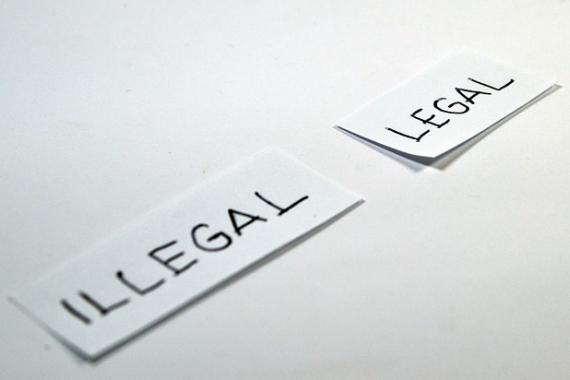 """Deux morceaux de papier sur lesquels sont inscrits les mentions """"illégal"""" et """"légal"""""""