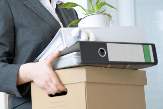 Femme portant une caisse contenant ses affaires de bureau