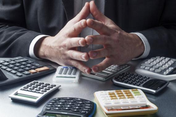 Homme se tenant assis les mains jointes devant plusieurs machines à calculer