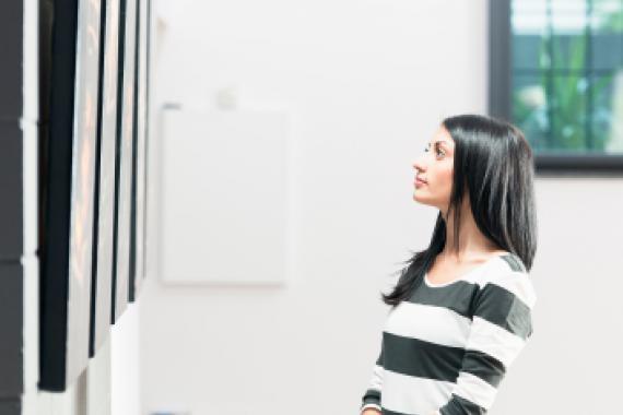 jeune femme observant une toile dans une galerie d'art