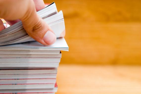 Main ouvrant un cahier dans une pile de documents