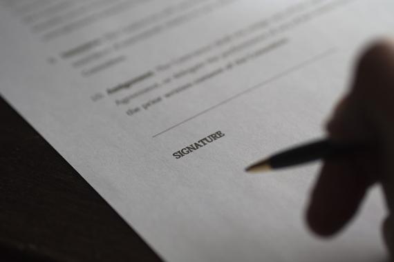 Main tenant un stylo, s'apprêtant à signer un document