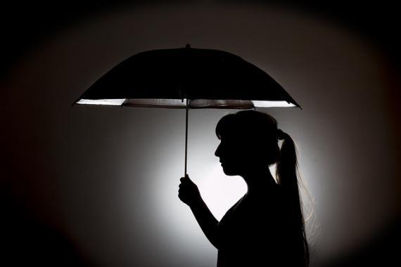 Silhouette d'une jeune femme tenant un parapluie