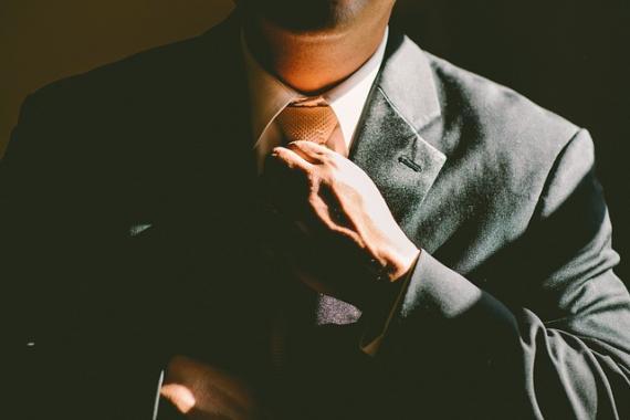 Homme en costume en train d'ajuster sa cravate