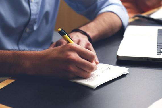 main qui écrit sur carnet