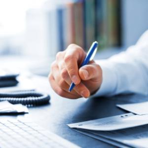 Main d'un homme qui tient un stylo sur son bureau