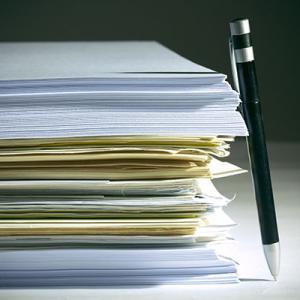 Stylo à bille appuyé sur une pile de documents