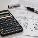 Une calculatrice et un stylo à bille posés sur un feuille de papier contenant des chiffres