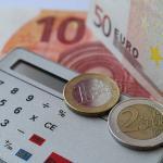 Deux pièces de monnaie (€) posées sur une machine à calculer placée à côte de billets de banque (€)