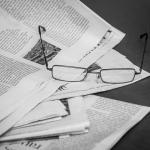 Paire de lunettes posée sur une pile de journaux