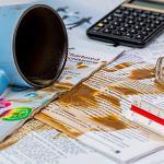 Tasse de café renversée sur un tas de documents en papier